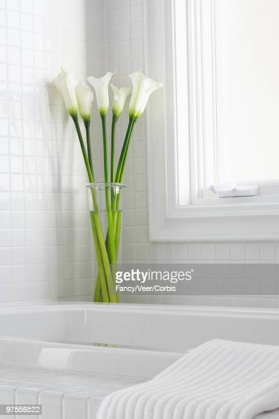 Vase of white calla lilies on edge of tub