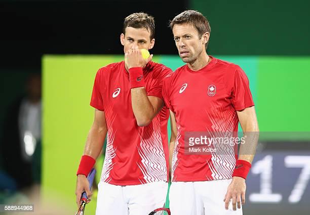 Vasek Pospisil and Daniel Nestor of Canada confer during the Men's Doubles Bronze medal match against Steve Johnson and Jack Sock of the United...