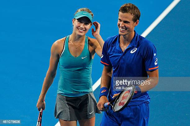 Vasek Pospisil and Eugenie Bouchard of Canada talk inbetween serves in the mixed doubles match against John Isner and Serena Williams of the United...