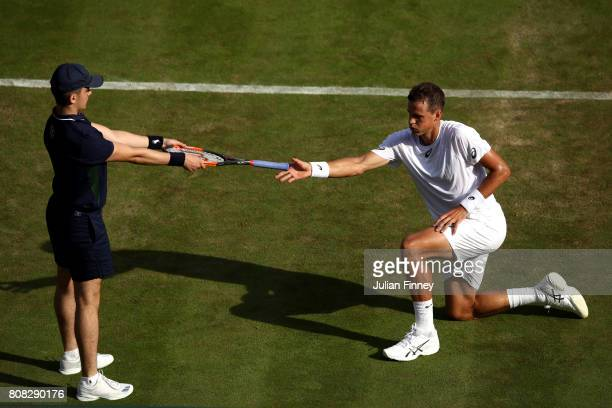 Vasek Pospisil of Canada collects his racket from a ball boy during the Gentlemen's Singles first round match against Dominic Thiem of Austria on day...