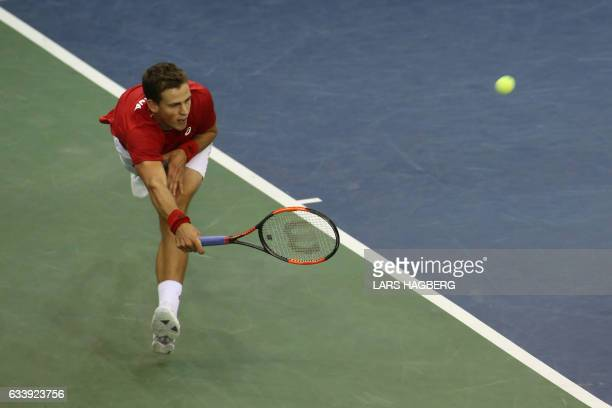 Vasek Pospisil of Canada hits a return against Daniel Evans of Great Britain during second set on the third day of Davis Cup first round between...