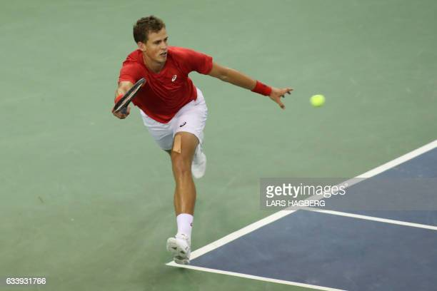 Vasek Pospisil of Canada hits a return against Daniel Evans of Great Britain during the fourth set on the third day of Davis Cup first round between...