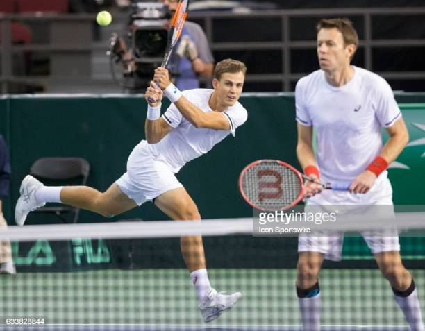 Vasek Pospisil of Canada reaches to return a shot past teammate Daniel Nestor to Dominic Inglot and Jamie Murray of Great Britain in men's doubles...