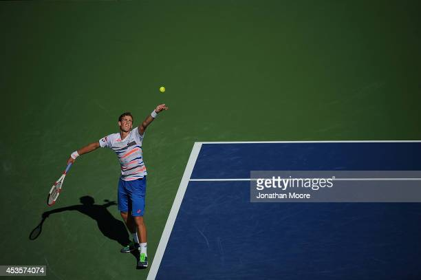 Vasek Pospisil of Canada serves against Roger Federer of Switzerland during a match on day 5 of the Western Southern open at Linder Family Tennis...