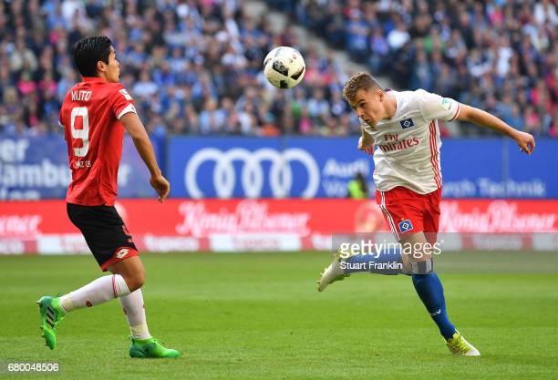 Vasilije Janjicic of Hamburg is challenged by Yoshinori Muto of Mainz during the Bundesliga match between Hamburger SV and 1 FSV Mainz 05 at...