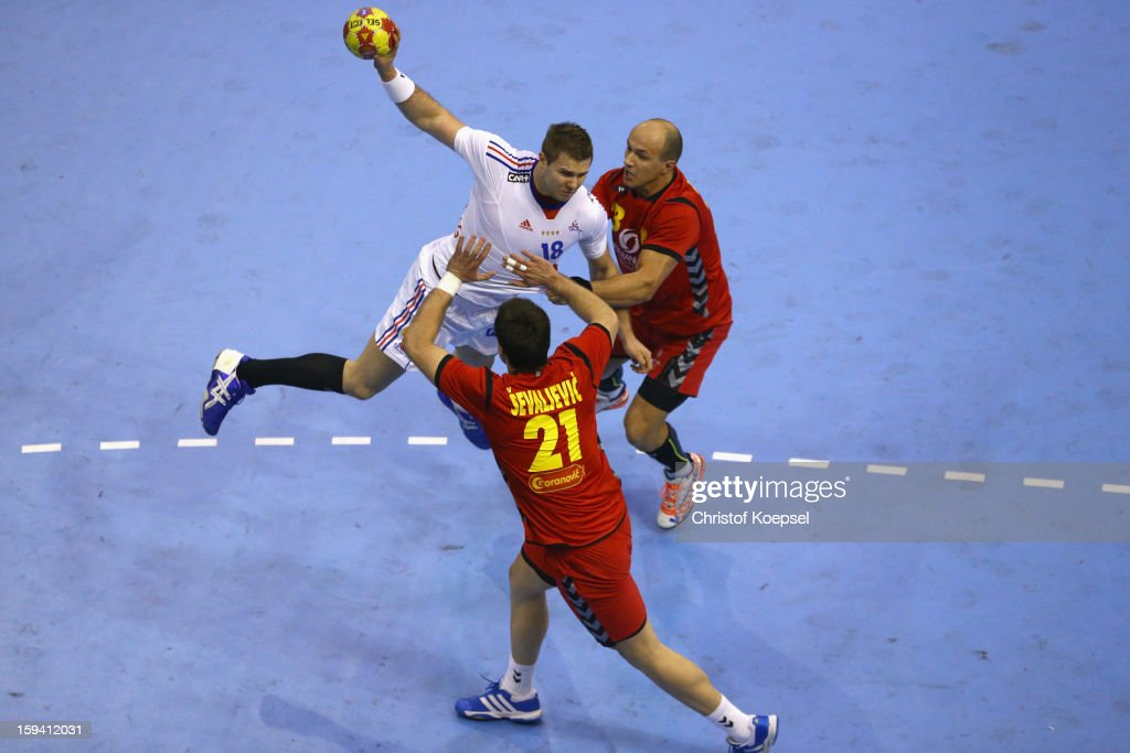 Vasko Sevaljevic of Montenegro (C) and Zoran Roganovic of Montenegro (R) defend against against William Accambray of France (C) during the premilary group A match between Montenegro and France at Palacio de Deportes de Granollers on January 13, 2013 in Granollers, Spain.
