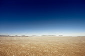 Flat desert scene with mountains at the horizon.