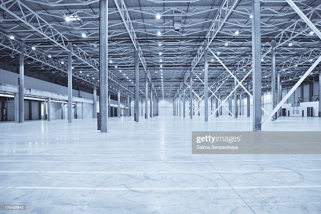 Vast empty warehouse with white floors and silver beams