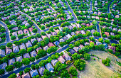 Vast Homes and Thousands of Houses Modern Suburb Development , green boxes of colorful houses below in a curved modern layout and design aerial drone view from high above suburbia