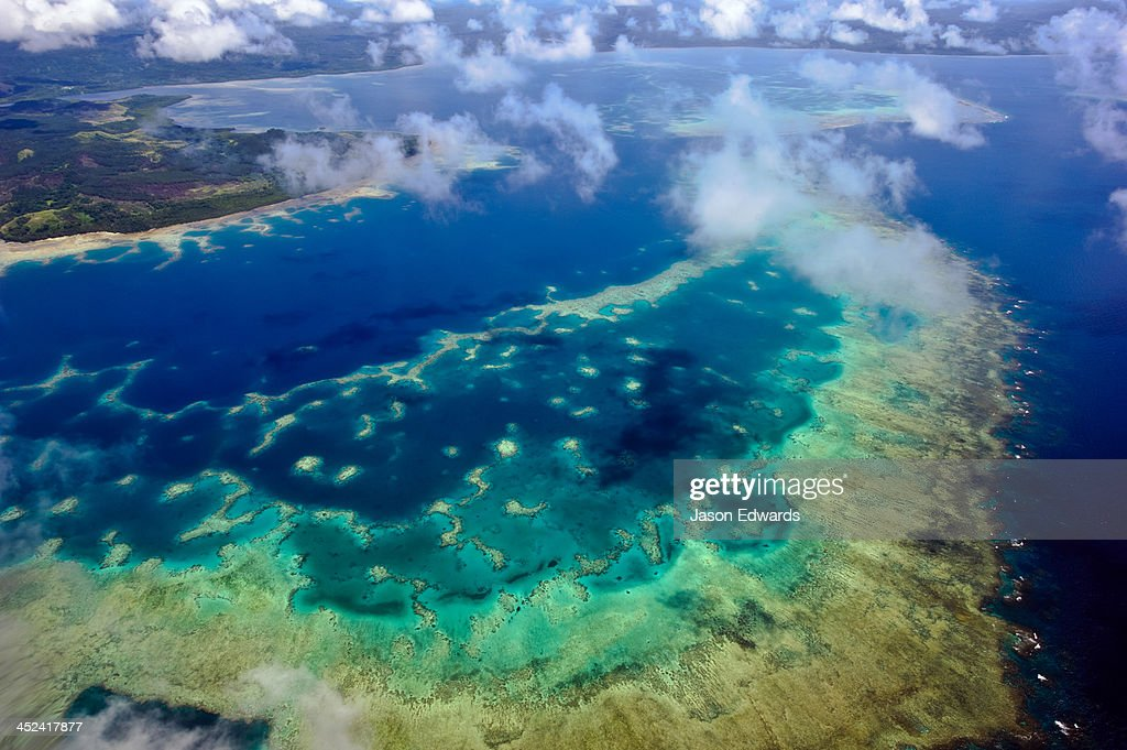 A vast pristine coral reef surrounding a tropical island.