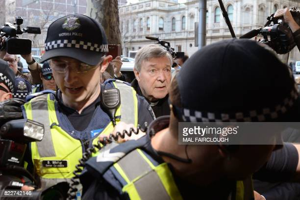 Vatican finance chief Cardinal George Pell arrives under heavy police protection for a hearing at the Melbourne Magistrates Court in Melbourne on...