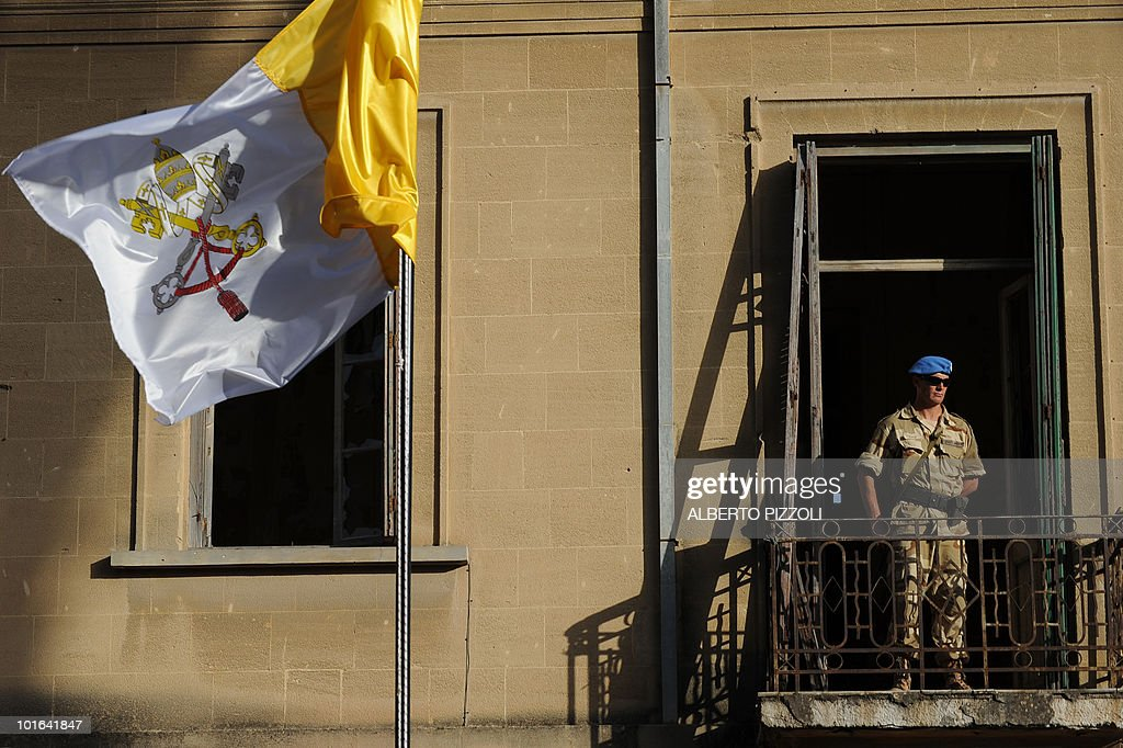 A Vatican flag flutters next to a British UN peacekeeper guarding a building facing Nicosia's Latin Church of the Holy Cross on the Green Line in the divided capital of Cyprus where Pope Benedict XVI celebrated mass on June 5, 2010, on the second day of his visit to the mainly Greek Orthodox east Mediterranean island.