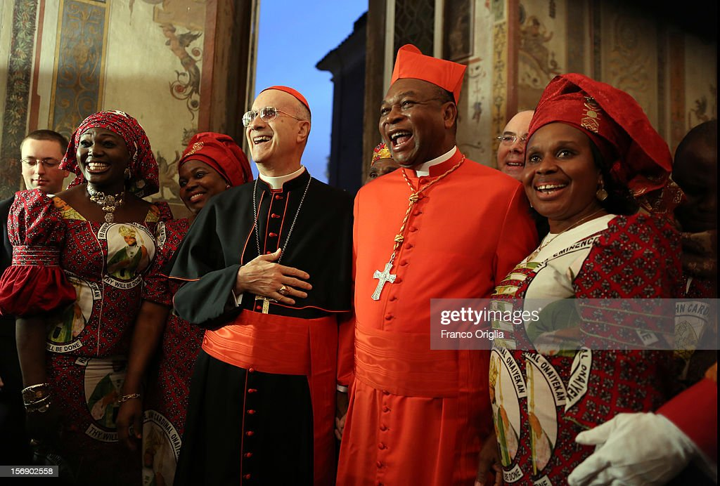 Vatican secretary of State cardinal Tarcisio Bertone (C) poses with newly appointed cardinal John Olorunfemi Onaiyekan (2ndR), archbishop of Abuja Nigeria, and his diocesans during the courtesy visits at the Sala Regia Hall at the end of the concistory held by Pope Benedict XVI on November 24, 2012 in Vatican City, Vatican. The Pontiff installed 6 new cardinals during the ceremony, who will be responsible for choosing his successor.