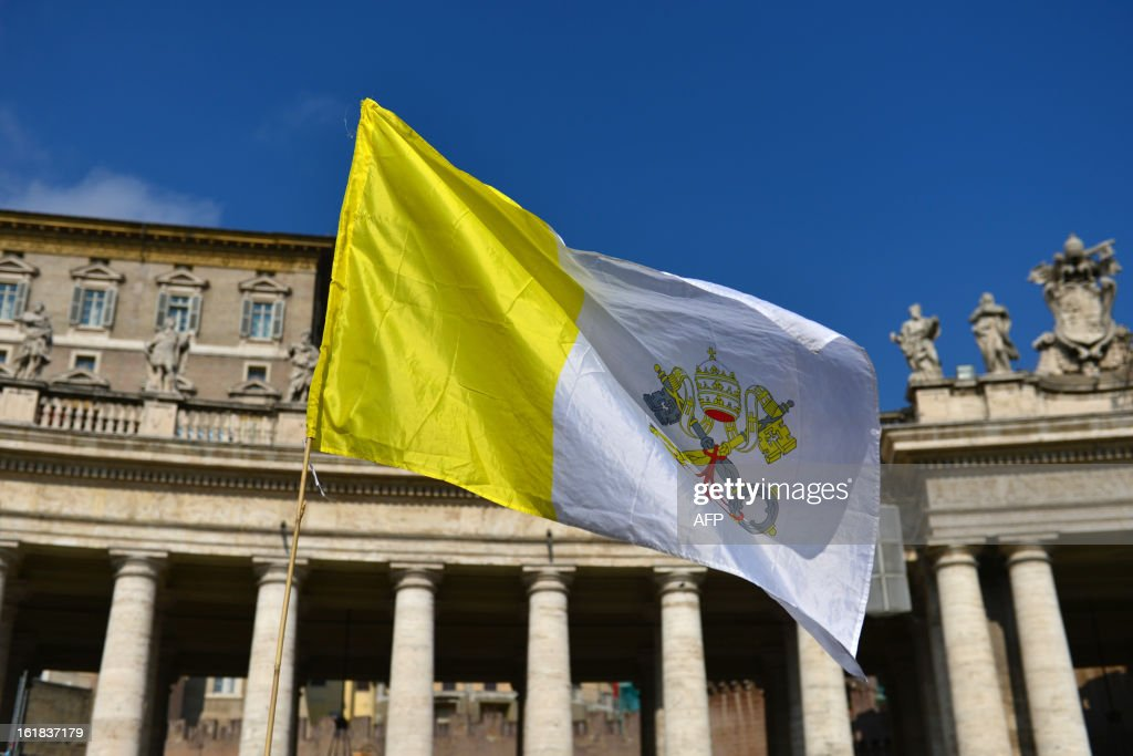 A Vatican's flag is displayed by faithful on St Peter's square after the Angelus prayer led by Pope Benedict XVI from the window of his appartments (Top-C) on February 17, 2013 at the Vatican. The Vatican the day before said it could speed up the election of a new pope as lobbying for Benedict XVI's job intensified amid speculation over who had the best chance to succeed him. AFP PHOTO / GABRIEL BOUYS