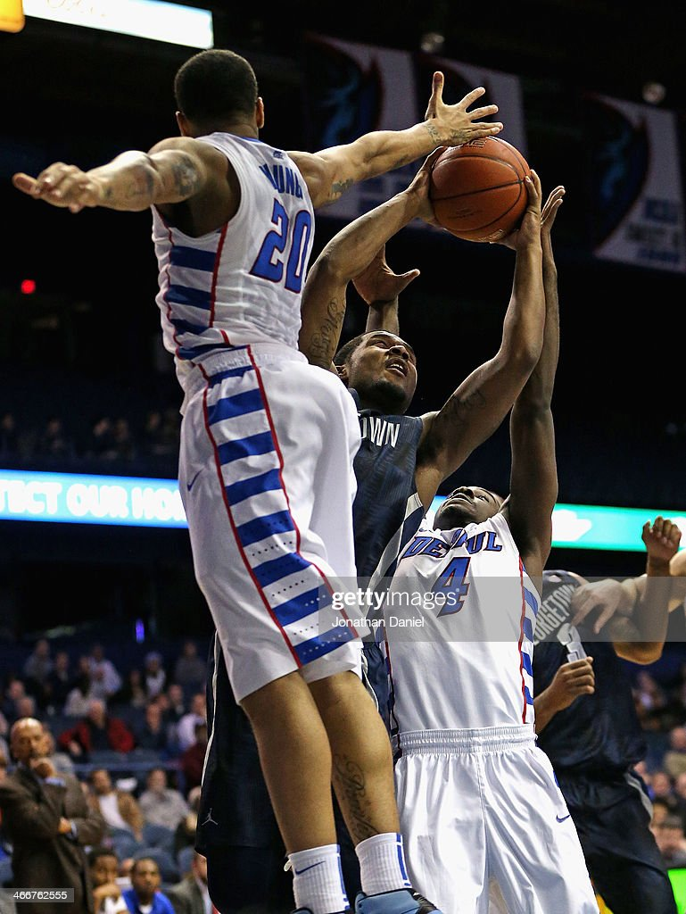 Vauntes SmithRivera of the Georgetown Hoyas puts up a shot between Brandon Young and Edwind McGhee of the DePaul Blue Demons at the Allstate Arena on...