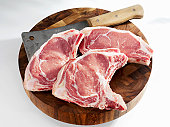 Veal cutlet and meat cleaver on chopping board