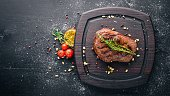 Veal steak with spices on the board. Top view. Free space for text. On a wooden background.