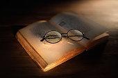 primo piano divecchio libro aperto con occhiali antichi