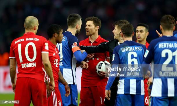 Vedad Ibisevic of Berlin argues with Xabi Alonso of Muenchen during the Bundesliga match between Hertha BSC and Bayern Muenchen at Olympiastadion on...