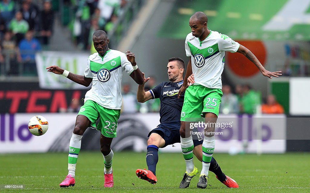 Vedad Ibisevic (C) of Berlin is attacked by Josuha Guilavogui (L) and Naldo (R) of Wolfsburg during the Bundesliga match between VfL Wolfsburg and Hertha BSC at Volkswagen Arena on September 19, 2015 in Wolfsburg, Germany.