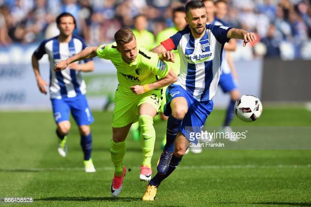 Vedad Ibisevic of Berlin is challenged by Philipp Max of Augsburg during the Bundesliga match between Hertha BSC and FC Augsburg at Olympiastadion on...