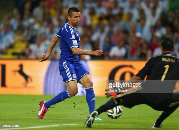 Vedad Ibisevic of Bosnia and Herzegovina shoots and scores his team's first goal past Sergio Romero of Argentina during the 2014 FIFA World Cup...