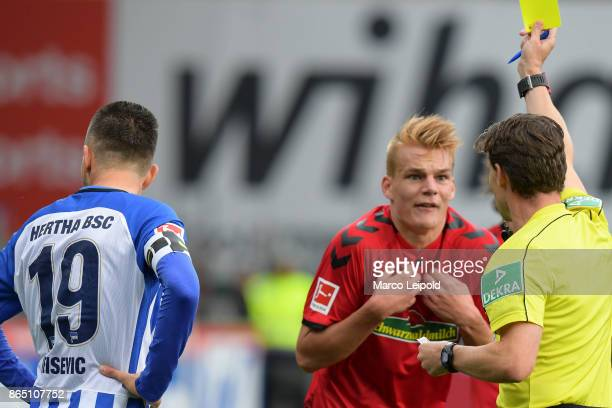 Vedad Ibisevic of Hertha BSC Philipp Leinhart of SC Freiburg and Referee Guido Winkmann during the game between SC Freiburg and Hertha BSC on October...