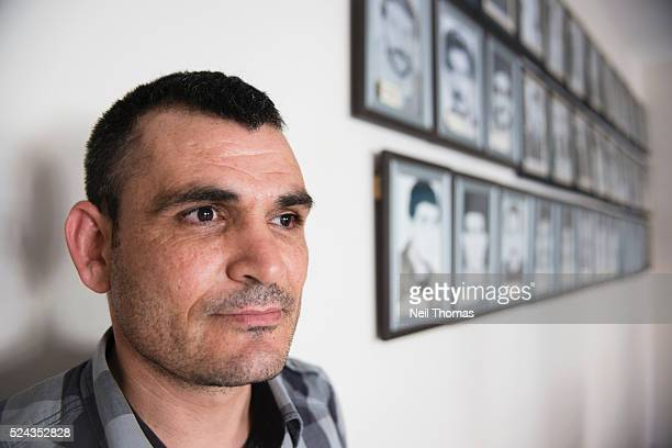 Vedat Kursun former EditorinChief of Azadiya Welat at the time the only Kurdish language newspaper in Turkey stands alongside portraits of Kurdish...