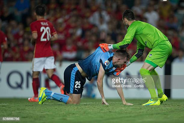 Vedran Janjetovic of Sydney FC helps up teammate Aaron Calver against Guangzhou Evergrande during the AFC Champions League match between Sydney FC...