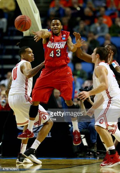 Vee Sanford of the Dayton Flyers passes the ball as LaQuinton Ross of the Ohio State Buckeyes defends during the second round of the 2014 NCAA Men's...