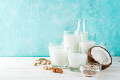 Vegan alternative food, set of various non-dairy milk - rice, coconut, almonds, pistachio, sesame, pumpkin seeds, soy, nuts, oatmeal, on light blue background, copy space