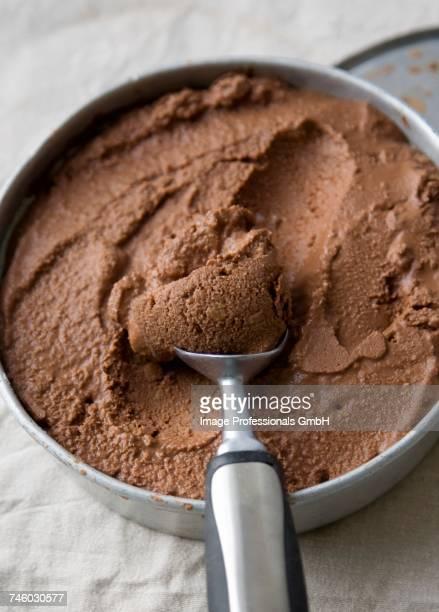 Vegan chocolate ice-cream in a metal dish with an ice cream scoop
