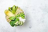 Vegan, detox green Buddha bowl recipe with quinoa, avocado, cucumber, spinach, tomatoes, mung bean sprouts, edamame beans, daikon radish. Top view, flat lay, copy space