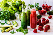 Fresh green smoothies and strawberry smoothie with ingredients on a light wooden background. Healthy detox drinks
