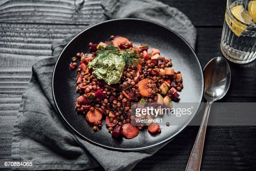 Vegan lentil vegetable dish with green pesto, parsley, dill, sunflowerseeds, carrot, beetroot, zucchini, onion, bell pepper