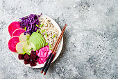 Vegan poke bowl with avocado, beet, pickled cabbage, radishes. Top view, overhead, flat lay