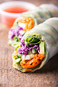 close up of fresh and vegan rice paper spring rolls with raw vegetables (cucumber, avocado, lettuce, carrots, red cabbage) inside, sweet chili dipping sauce behind, isolated over dark, wooden backgrou