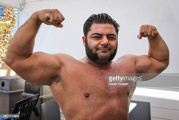 Vegan strongman Patrik Baboumian flexes his arms after he breaks a world record by carrying 555 kilos 10 metres on the West Jet stage at the...