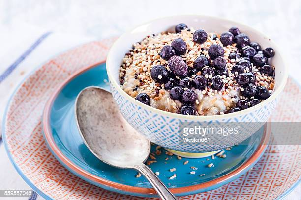 Vegan superfood breakfast with porridge, almond milk, blueberries and roasted quinoa