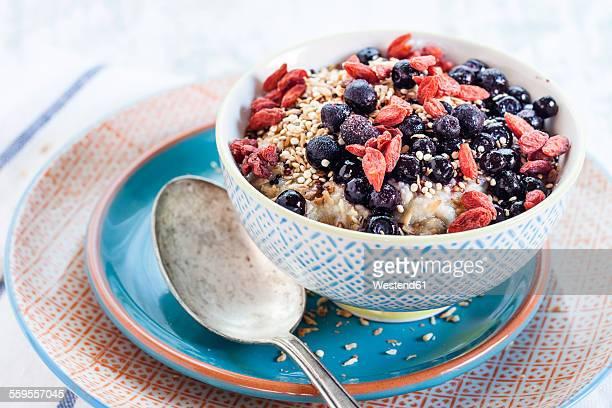 Vegan superfood breakfast with porridge, almond milk, blueberries, roasted quinoa, and goji berries