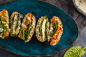 Vegan sushi sandwich onigirazu with tofu and vegetables. Colorful japan sandwich onigirazu with tofu, sweet potato, avocado and tahini. Trend vegan food concept.
