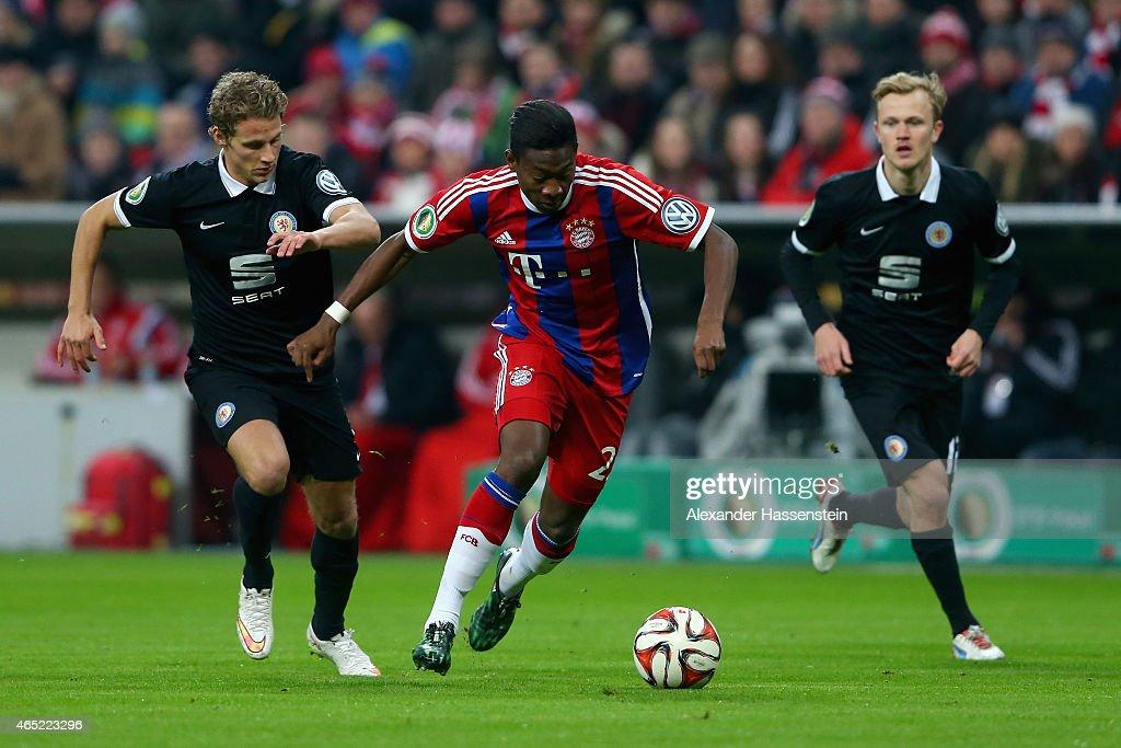Vegar Eggen Hedenstad of Eintracht Braunschweig challenges David Alaba of FC Bayern Muenchen during the round of 16 DFB Cup match between FC Bayern...