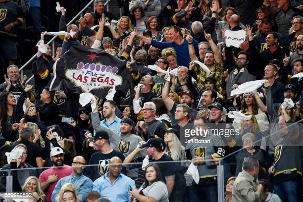 Vegas Golden Knights fans celebrate after their team scores a goal against the Arizona Coyotes during the Golden Knights' inaugural regularseason...