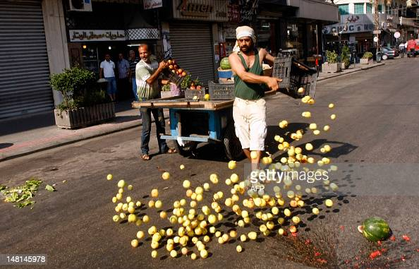 A vegetable and fruit vendor empties a crate containing apples along a street in the southern Lebanese port city of Sidon on July 11 as some 160...