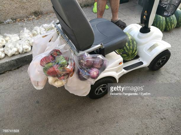 Vegetable Hanging On Mobility Scooter By Man On Sidewalk