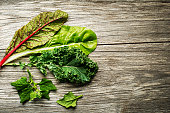 Vegetable healthy green leaves. Kale, swiss chard and spinach on wooden background