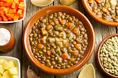 Vegetable lentil soup on a clay pot and admixtures on wooden table
