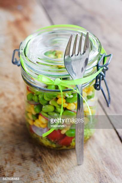 Vegetable salad with corn, fava beans and red radishes in preserving jar