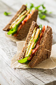 Vegetable sandwich with zucchini burger, cheese, ruccola and tomatoes, baking paper, rustic wood background