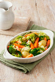 Vegetable selection consisting of broccoli, carrots, new potatoes and cabbage in white serving dish on green cloth